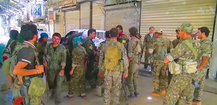Members of the Syrian Democratic Forces discuss further operations 12 August 2016 in the Syrian city of Manbij shortly after a fierce fight to liberate it from Islamic State control.