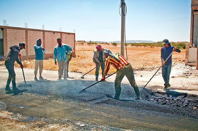 Men repair a road 11 July 2018 in a village outside Manbij, Syria.