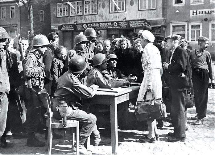 "A military government ""spearhead"" (I Detachment) of the 3rd U.S. Army answers German civilian questions in April 1945 at an outdoor office in the town square of Schlesingen ,Germany."