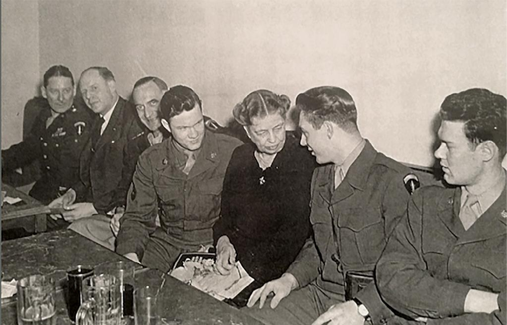 Sgt. Verlan Gunnell (<em>second from right</em>) speaks with Eleanor Roosevelt <em>(third from right</em>) in this photograph from World War II. Also pictured (<em>from left</em>) are Brig. Gen. James Edmunds, administrative officer of the Office of Military Government, United States (OMGUS