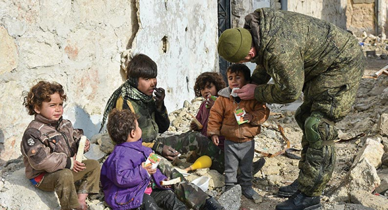A Russian sapper administers relief to a group of destitute children 23 December 2016 in Aleppo, Syria
