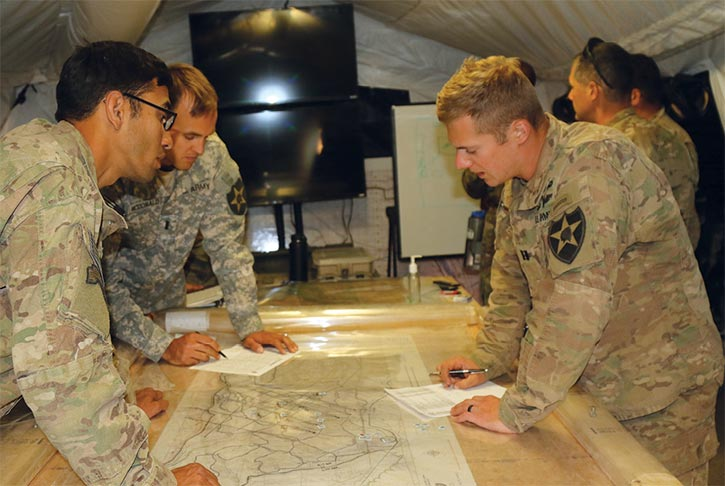 Capt. Wade Redenius (<em>right</em>) discusses the plan for an upcoming mission with 1st Lt. Ross McDonald and 2nd Lt. Tony Eshoo