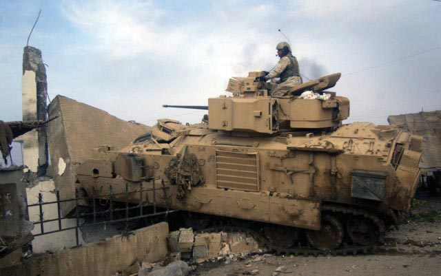 Bradley fighting vehicle turret gunner Sgt. Ramel Colclough fires at Iraqi positions with his 25 mm cannon as his vehicle breaches an obstacle.
