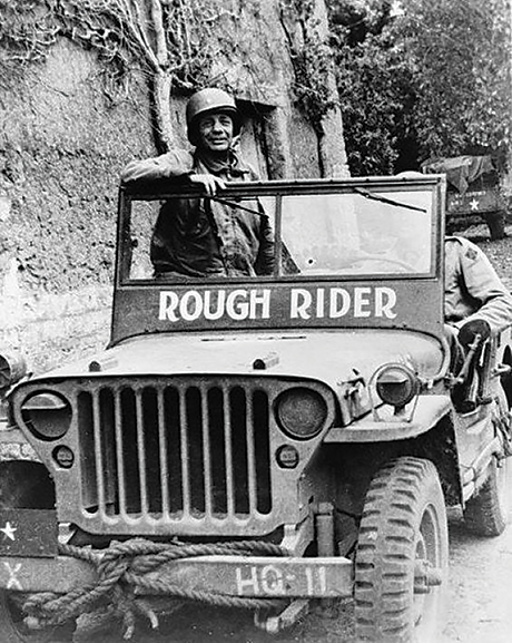 "In his jeep, ""Rough Rider,"" Brig. Gen. Theodore Roosevelt Jr. moves with frontline troops 6 June 1944 away from Utah Beach in Normandy, France."