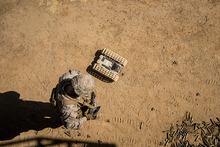 "A marine with 3rd Battalion, 5th Marine Regiment looks down at an autonomous ""dragon fire"" system"