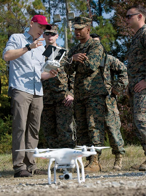Ryan Mcalinden (left), University of South California's director of modeling, simulation, and training, demonstrates how to operate the Phantom 3 drone