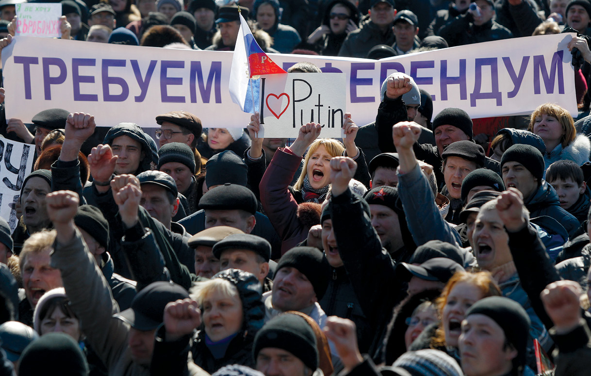"People hold a banner reading ""We demand a referendum"" as they shout slogans during a pro-Russian rally 8 March 2014 in Donetsk, Ukraine, and as Russia was reported to be reinforcing its military presence in Crimea. (Photo by Sergei Grits, Associated Press)"