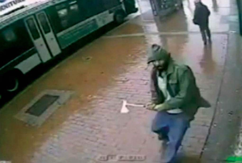 A screenshot from a surveillance camera shows Zale Thompson, labeled a self-radicalized Muslim, raising a hatchet 23 October 2014 moments before striking a group of four uniformed New York Police Department (NYPD) officers in Jamaica, Queens, New York. Thompson was shot dead by two of the officers. (Photo courtesy of NYPD)