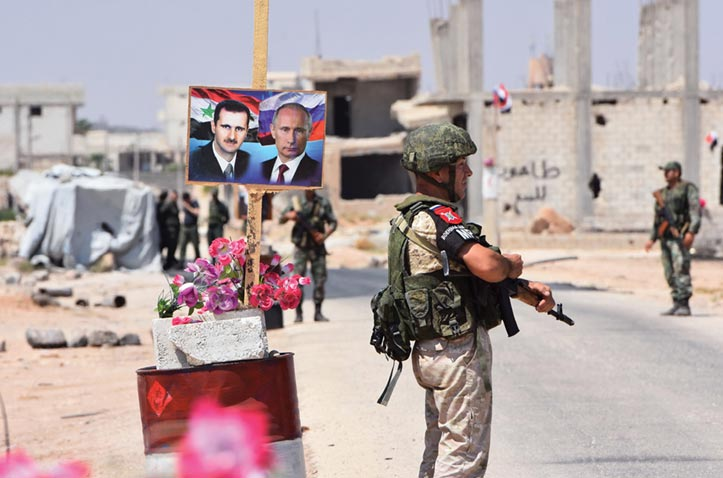 Members of Russian and Syrian forces stand guard near posters of Syrian President Bashar al-Assad and his Russian counterpart President Vladimir Putin 20 August 2018 at the Abu Duhur crossing on the eastern edge of Idlib Province in Syria.