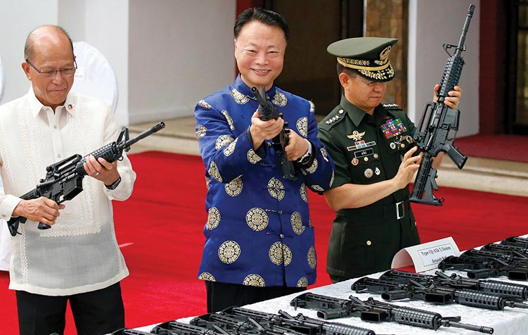 Philippine Defense Secretary Delfin Lorenzana (<em>left</em>), Chinese Ambassador to the Philippines Zhao Jianhua, and Philippine Armed Forces Chief Gen. Eduardo Ano (<em>right</em>) inspect Chinese-made CQ-A5b assault rifles 5 October 2017 during a turnover ceremony at Camp Aguinaldo in Quezon City, Philippines.