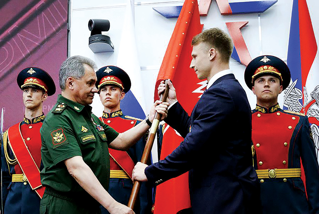 Russian Minister of Defence General of the Army Sergei Shoigu presents the flag to the chief of the Yunarmiya staff, Olympic champion Dmitry Trunenkov, 2 June 2016 during the first rally of the all-Russian military-patriotic social movement Yunarmiya at the military-themed Patriot Park in Moscow. (Photo courtesy of the Ministry of Defence of the Russian Federation)