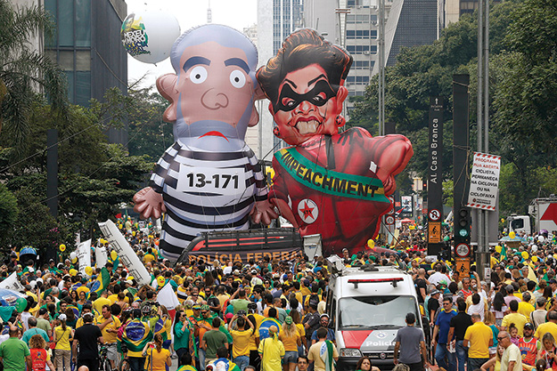 "Demonstrators parade large inflatable dolls depicting Brazil's former President Luiz Inácio Lula da Silva in prison garb and then President Dilma Rousseff dressed as a thief with a presidential sash that reads ""Impeachment"" 13 March 2016 in São Paulo."