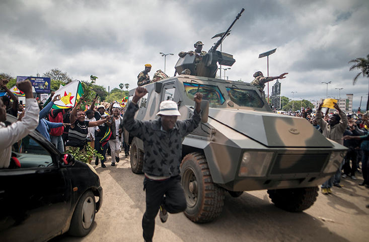 People cheer a passing Zimbabwe Defense Force military vehicle 18 November 2017