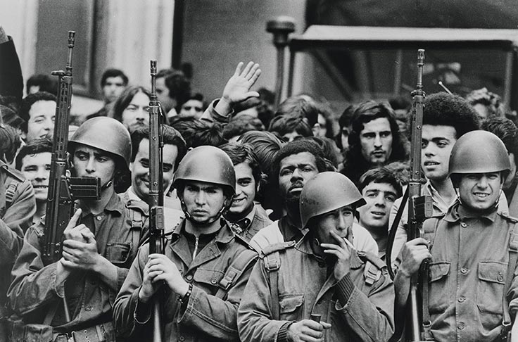 "Soldiers on guard enjoy the celebration with Portuguese citizens following the successful ""Carnation Revolution"" military coup 25 April 1974 in Lisbon, Portugal. The coup ended the four-decade-long dictatorship of the Estado Novo regime. (Photo by Alfredo Cunha, courtesy of Fundo Alfredo Cunha/Fundação Mário Soares, Casa Comum, http://casacomum.org/cc/visualizador?pasta=10079.001.029#)"
