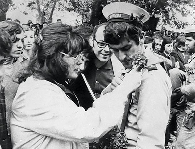 A woman gives a carnation to a soldier 25 April 1974 as massive crowds celebrate the restoration of democracy in Lisbon, Portugal.