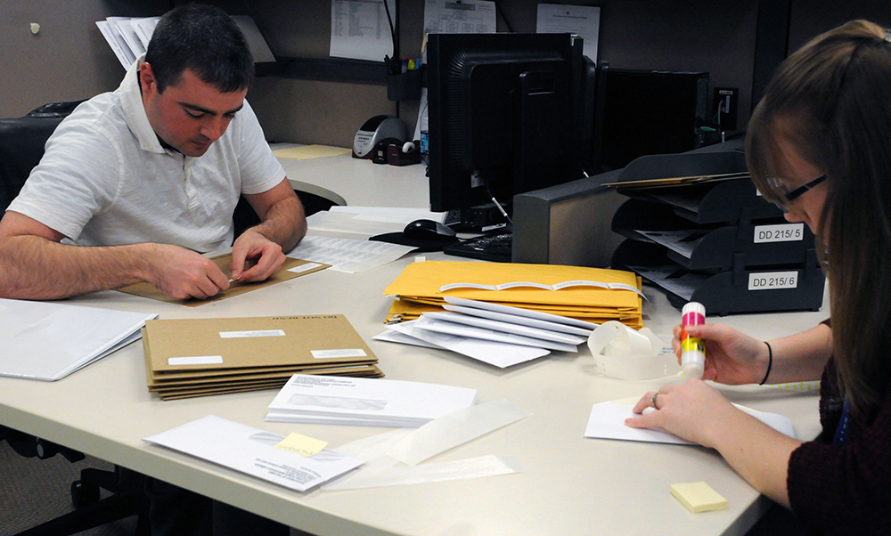 Contractors for the Transition Branch at Human Resources Command at Fort Knox, Ky., prepare forms to mail to transitioning Soldiers. (Photo by Martha C. Koester / NCO Journal)