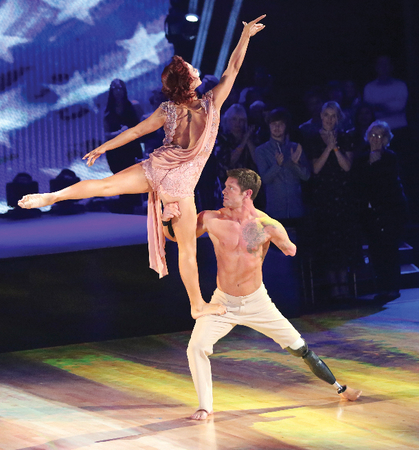 "Noah Galloway lifts his partner Sharna Burgess during the contemporary dance portion of ""Dancing With The Stars."" Galloway and Burgess danced to Toby Keith's ""American Soldier."" Galloway's one-armed lift brought the audience members to their feet. (Photo courtesy of ABC's ""Dancing With The Stars"")"