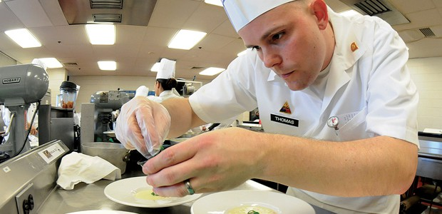 Military Culinary chef preparing a dish.