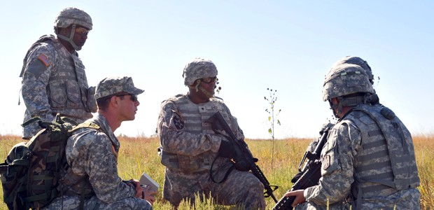 Army military members huddled in group of 5 in a field.