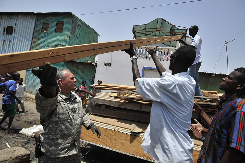 Staff Sgt. Wayne Teegardin, from the 478th Civil Affairs Battalion, Combined Joint Task Force–Horn of Africa, unloads lumber in the Boulas commune of Djibouti City on Aug. 12, 2009. The lumber was used to rebuild 21 homes destroyed in a fire. (Department of Defense photo by Navy Mass Communication Specialist 2nd Class Jesse B. Awalt)