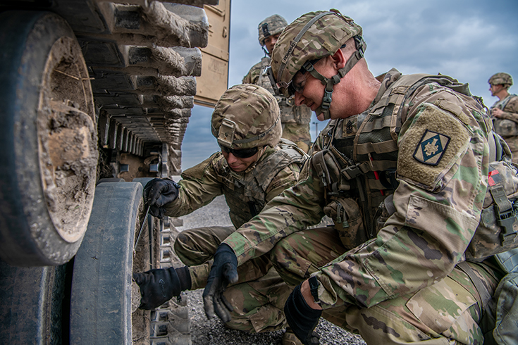 U.S. Army 1st Sgt. Richard McCormick, right, Able Company first sergeant, mentors Pvt. 1st Class Lathan McLeod, a multiple launch rocket system crewmember, on how to properly clear obstructions from a vehicles tracks after prolonged operations at Fort Sill, Okla., March 29, 2019