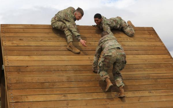 U.S. Army Pfc. Kael Mullins, (left) and Pfc. Travis D. Carter, (right), both signal support specialists with the 534th Signal Company, 4th Special Troops Battalion, 4th Sustainment Brigade, help Pfc. Tamara Borja, (center), a signal support specialist, over an obstacle at Fort Carson, Colo., May 8, 2019.