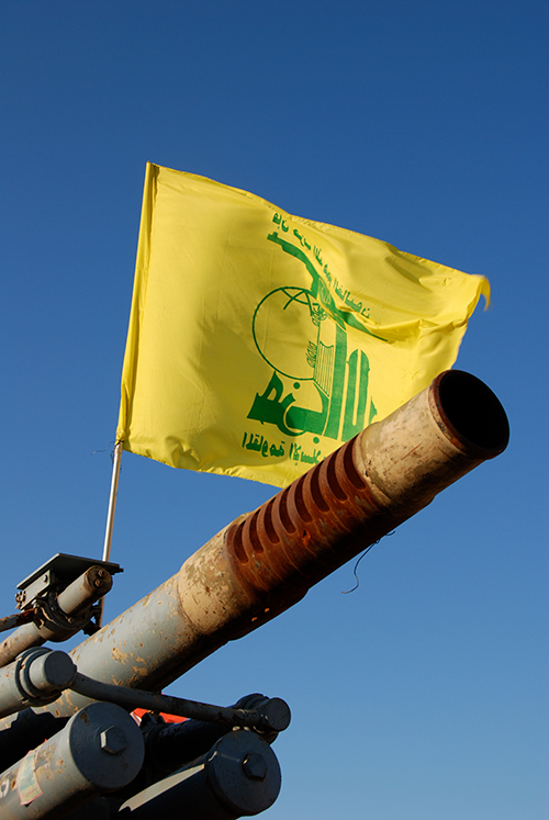 A Hezbollah flag flying over an abandoned artillery piece