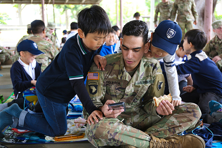 A Soldier assigned to the 38th Air Defense Artillery Brigade, shows LCA Kokusai Elementary School students a game on his cellphone