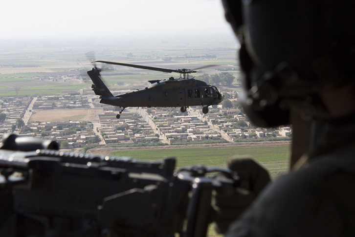 A U.S. Army UH-60 Blackhawk door gunner watches as another UH-60 Blackhawk flies over Syria during a visit by Special Presidential Envoy