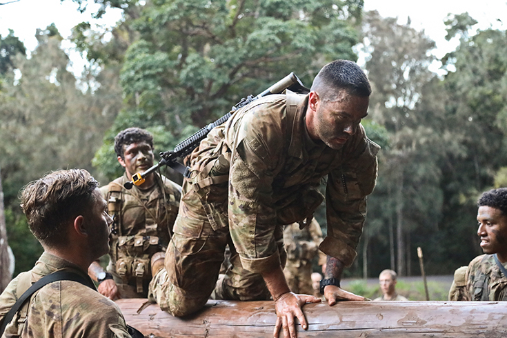 U.S. Army Soldiers work together in teams to complete the Green Mile physical endurance course