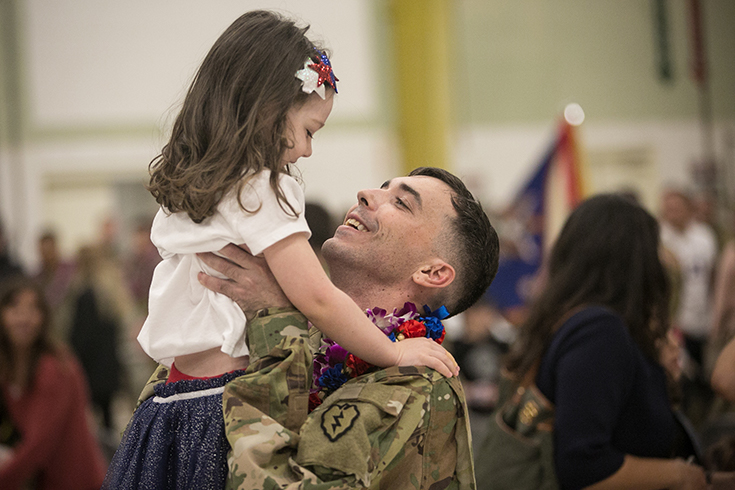A U.S. Army Soldier assigned to the Hillclimbers, 3rd Battalion, 25th Aviation Regiment (General Support Aviation Battalion) reunites with family during a welcome home ceremony