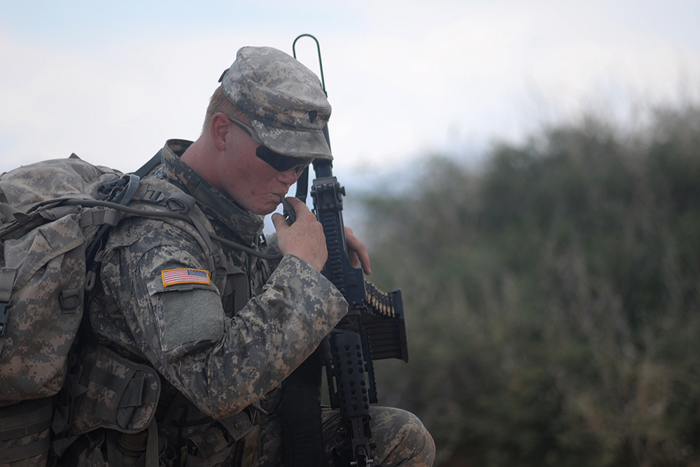Spc. Riley Ladd of 4th Battalion, 17th Infantry Regiment, 1st Brigade Combat Team (Stryker), 1st Armored Division takes a break to drink water while on a field exercise during the new Desert Warrior course at Fort Bliss, Texas. (Photo by Meghan Portillo/NCO Journal)