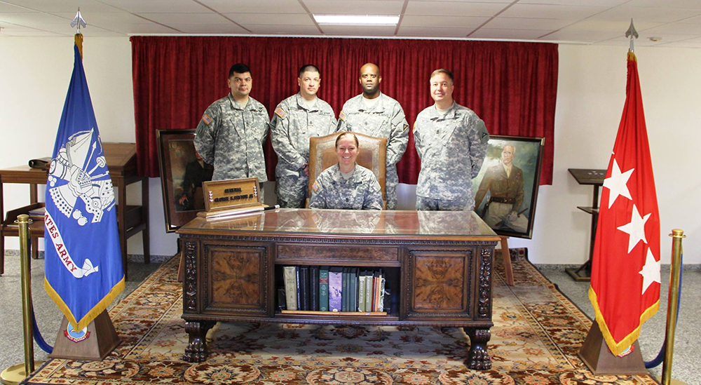 "U.S. Army Europe's command sergeant major, Command Sgt. Maj. Sheryl Lyon, sits at ""The Patton Desk"" at the main entrance to the 7th Army NCO Academy in Grafenwoehr, Germany. The desk belonged to Gen. George S. Patton during World War II. (Photo courtesy of 7th Army NCO Academy)"