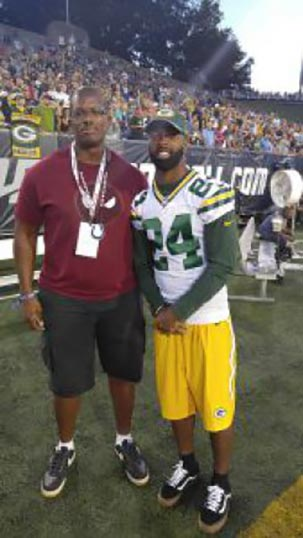 >Staff Sgt. Kyle Richardson stands with Green Bay Packers cornerback Jarrett Bush during the Pro Football League Hall of Fame Game
