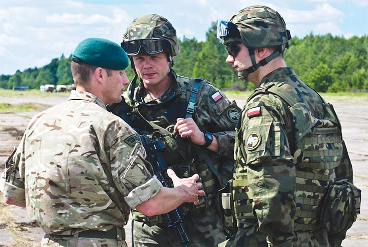 Maj. Simon Cox, commander of X-Ray Company, 45 Commando Royal Marines, talks with soldiers from 7th Air Cavalry Battalion