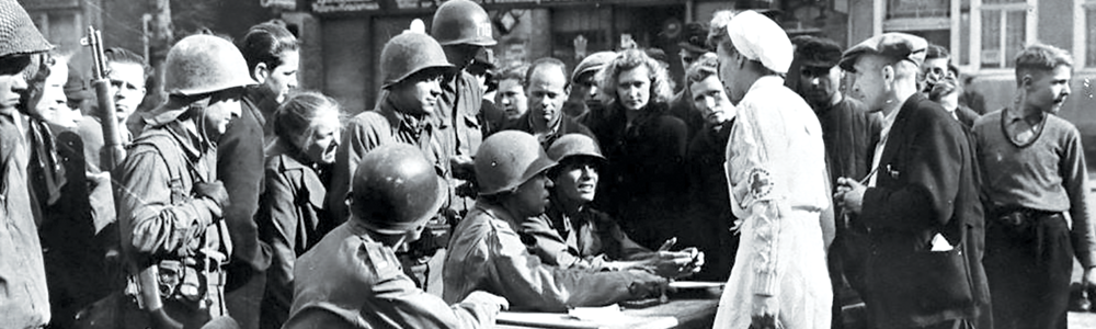 "A military government ""spearhead"" (I Detachment) of the 3rd U.S. Army answers German civilian questions in April 1945 at an outdoor office in the town square of Schlesingen ,Germany. I Detachments moved in the wake of division advances to immediately begin the process of civilian stabilization and normalization. (Photo from book, The U.S. Army in the Occupation of Germany 1944-1946, by Earl F. Ziemke)"