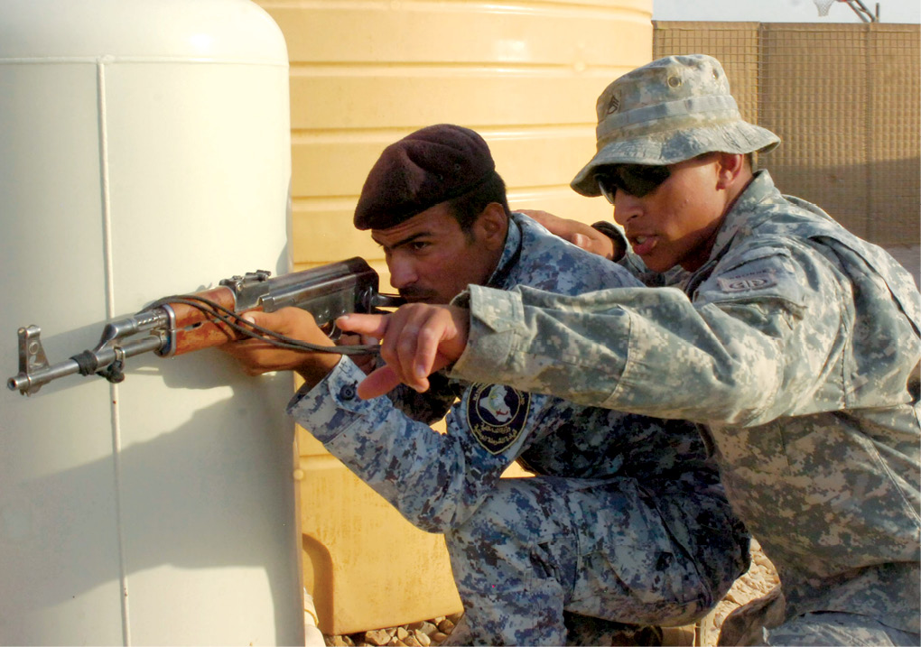 Staff Sgt. Damian Remijio instructs an Iraqi National Police (NP) officer assigned to the 3rd NP Brigade, 1st NP Division, to keep his sights on a door during a training event 24 June 2009 at Forward Operating Base Hammer, located outside of eastern Baghdad, Iraq. (Photo by Sgt. 1st Class Alex Licea, U.S. Army)