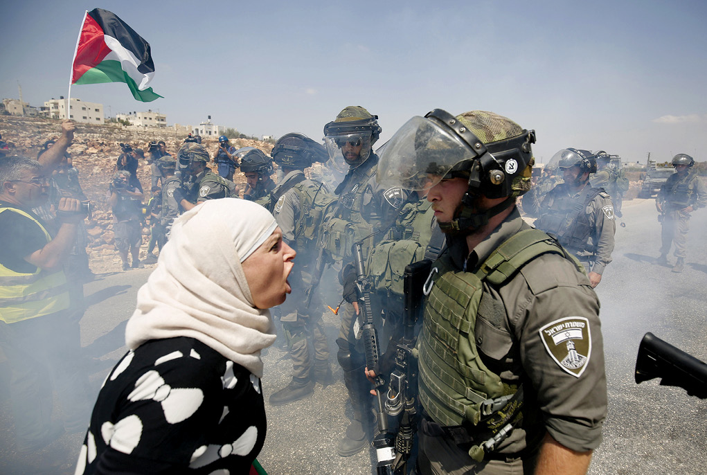 A Palestinian woman argues with an Israeli border policeman 4 September 2015 during a protest against Jewish settlements in the West Bank village of Nabi Saleh near the Palestinian city of Ramallah. (Photo by Mohamad Torokman, Reuters)