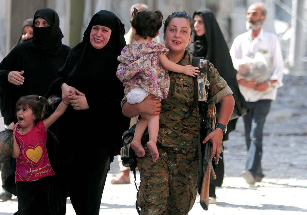 A Syrian Democratic Forces (SDF) fighter helps civilian refugees, including large numbers of  women and children, who were evacuated by the SDF from an Islamic State-controlled neighborhood of Manbij 12 August 2016 in Aleppo Governorate, Syria. The SDF said the Islamic State was using civilians as human shields. (Photo by Rodi Said, Reuters)