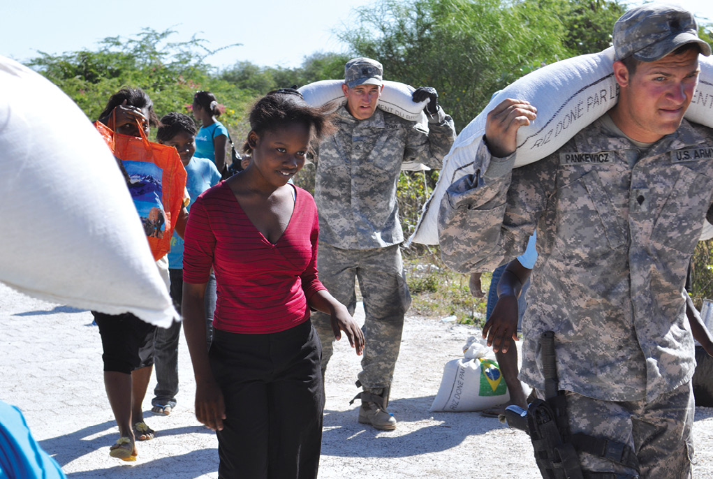 Soldiers assist Haitian citizens 2 February 2010 by carrying bags of food from the World Food Program distribution point. U.S. soldiers were instrumental in initially opening nine distribution points around Haiti.