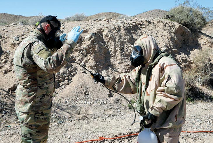 A soldier from the 44th Chemical Company sprays water on another soldier who was exposed to a simulated chemical agent at a field decontamination station