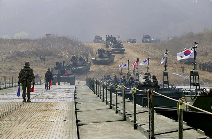 Soldiers drive 68-ton M1A2 Abrams main battle tanks and 27-ton M2A3 Bradley infantry fighting vehicles across a floating bridge over the Imjin River 8 April 2016 near Seoul, South Korea