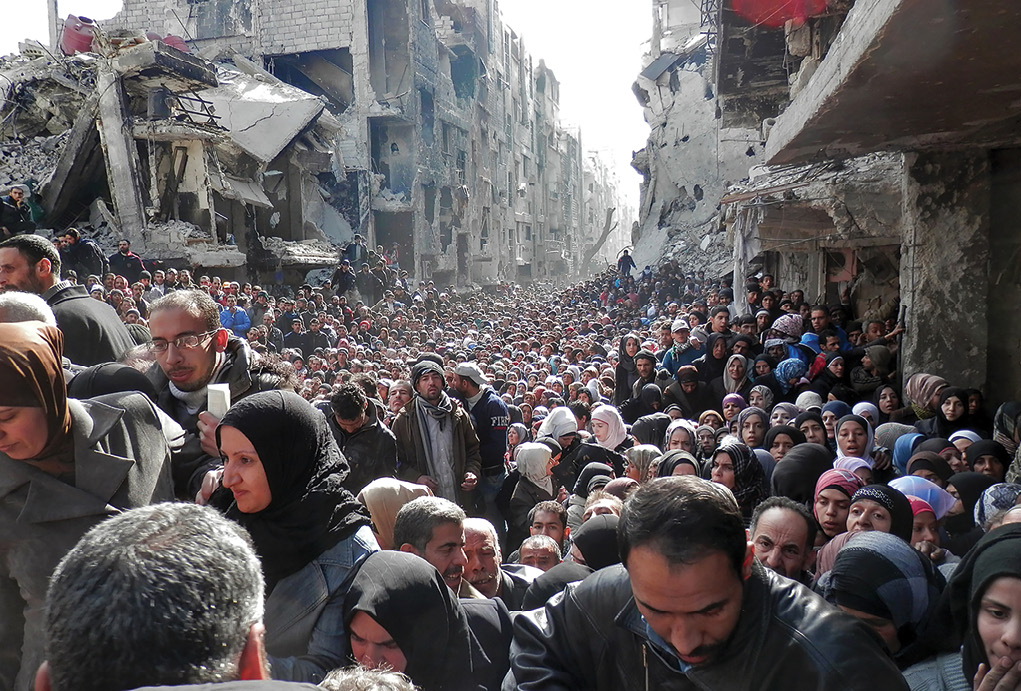Thousands of desperate residents flood a destroyed main street January 2014 in Damascus, Syria, to meet aid workers from the United Nations Relief and Works Agency (UNRWA). The UNRWA was able to complete its first humanitarian food distribution in Yarmouk Camp there after almost six months of siege. (Photo courtesy of UNRWA)