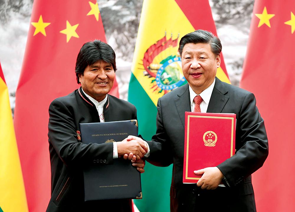O Presidente da China, Xi Jinping, cumprimenta o Presidente boliviano Evo Morales no Grande Salão do Povo, em Pequim (Beijing), 19 Jun 18. A China pretende realizar investimentos expressivos na economia boliviana, sobretudo, em sua infraestrutura energética. A Bolívia é o único país sul-americano que abrange, concomitantemente, as regiões andina, platina e amazônica. (Kyodo via AP Images)