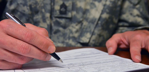 Army soldier in uniform filling out form, pen in hand