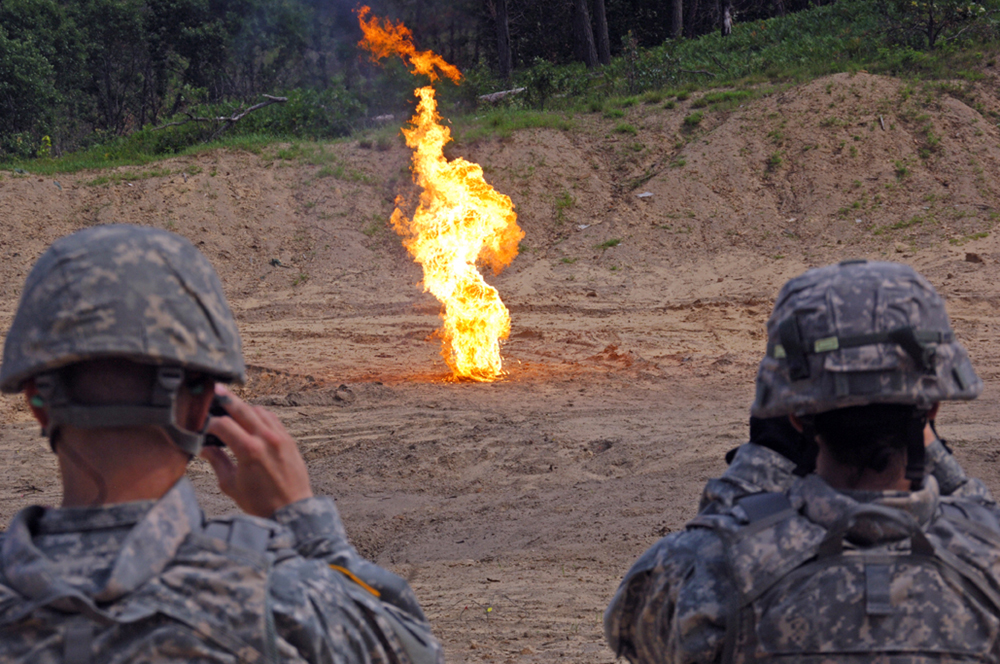 At a Fort McCoy, Wis., demolition range, students in the 89B ammunition specialist course watch a powder bag fire from a 105mm HE round. The students were learning how to dispose of the black powder after it's turned into an ammunition supply point. (Photo by Jonathan (Jay) Koester / NCO Journal)