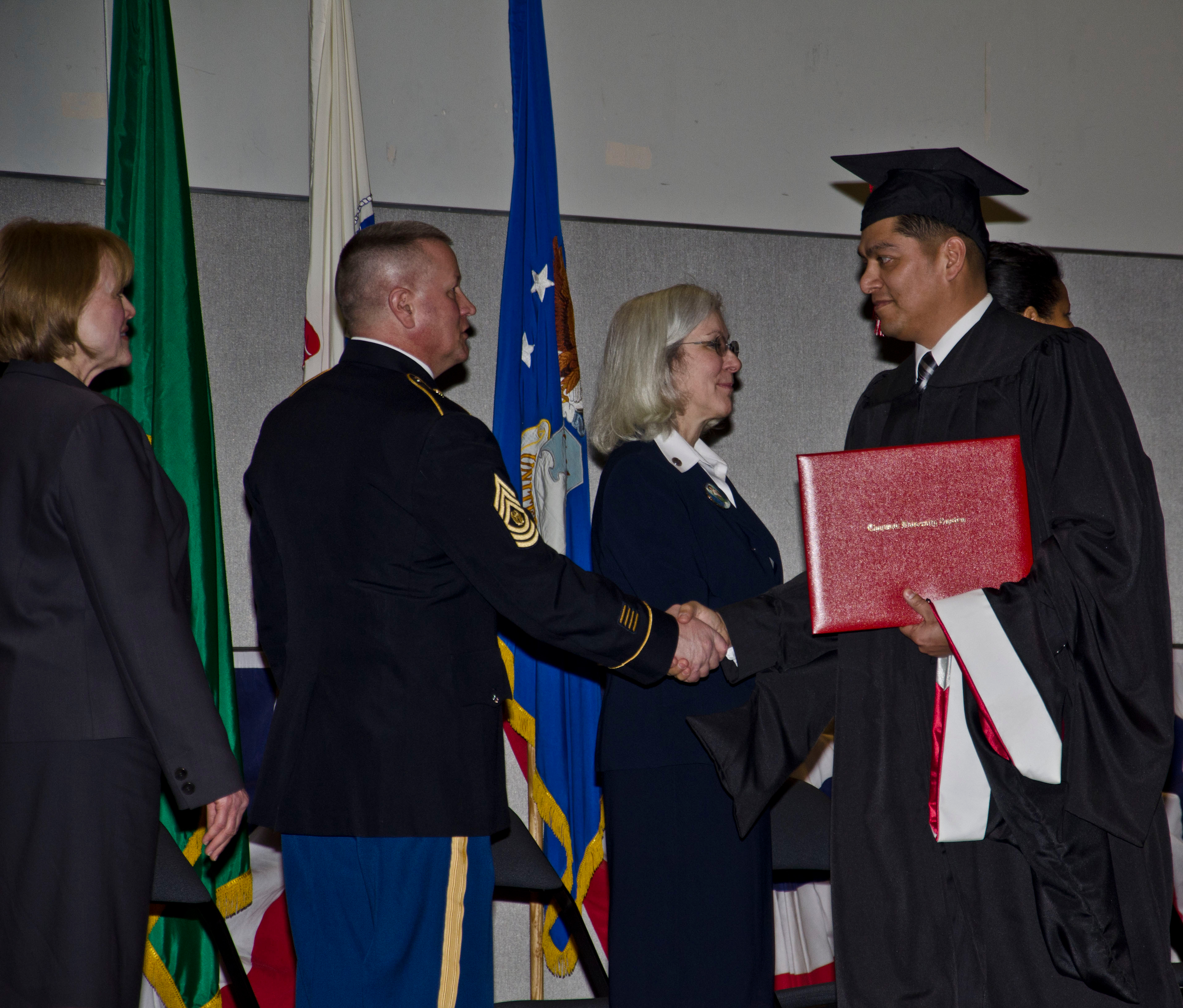 Master Sgt. Ramiro R Cantu is presented his master's degree during the first combined college graduation ceremony for Joint Base Lewis-McChord