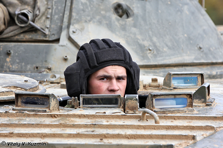A BMP-2 (*amphibious infantry vehicle) driver looks out of the driver's hatch during the annual inspection by the commission of the Western Military District in October of 2011. (Image courtesy: Vitaly Kuzmin*)