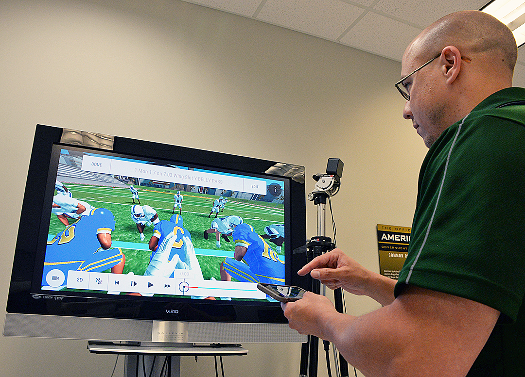"Army Game Studio designer Tony Donatellie demonstrates some of the tools available in ""Go Army Edge Football."" The screen shows a play from a player's perspective. (Photo by Clifford Kyle Jones)"