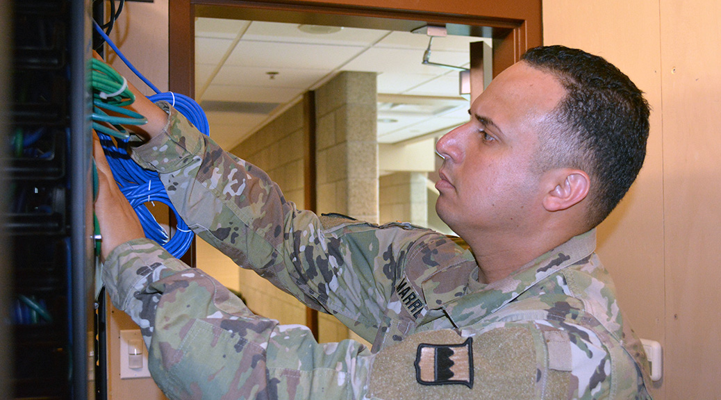 Staff Sgt. Hector Marrero, an information technology specialist assigned to the 80th Training Command, trouble shoots computer connectivity in The Army School System Training Center's Network Operation Command, in Grand Prairie, Texas. As part of the transition to Army University, experts such as Marrero will have an easier time receiving civilian credentials for their Army expertise. (Photo by Sgt. 1st Class Phillip Eugene)
